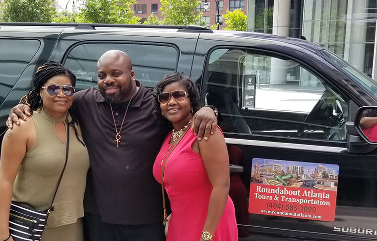 Omar and two women in front of a company vehicle