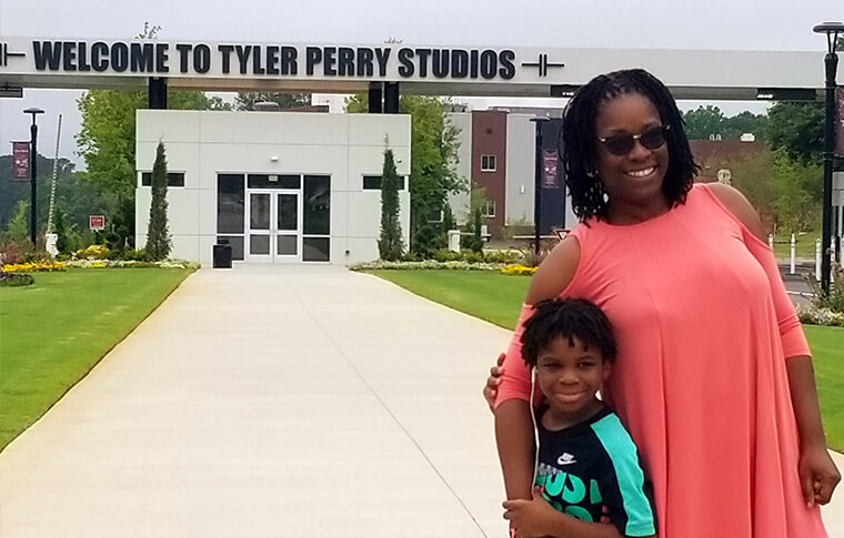 Woman and young boy in front of Tyler Perry Studios