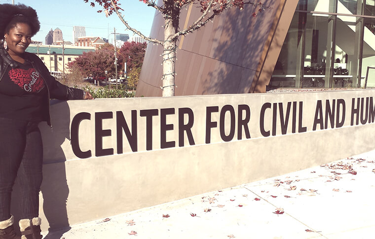 Woman posing in front of a sign that reads: center for civil and human rights