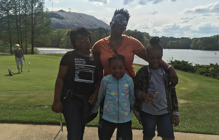 Family smiling in front of a golf course at Stone Mountain