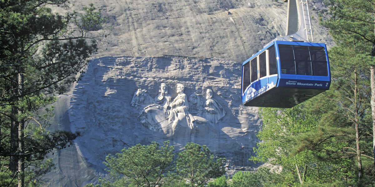 cable car with stone mountain and sculpture carving in background
