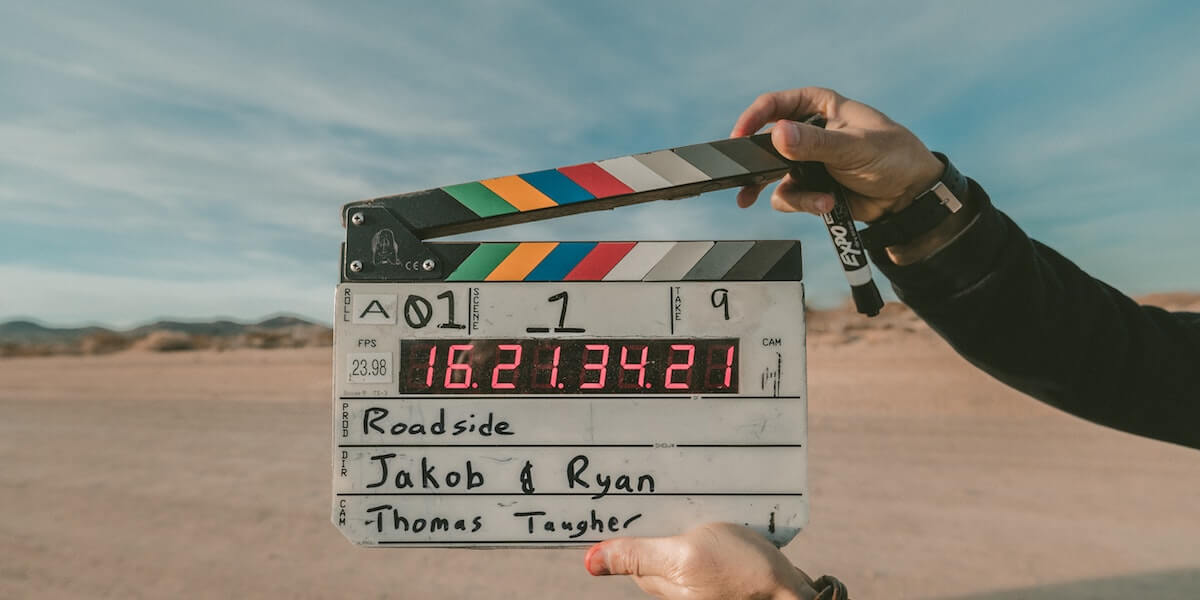 a clapperboard being held in front of a film set in the desert