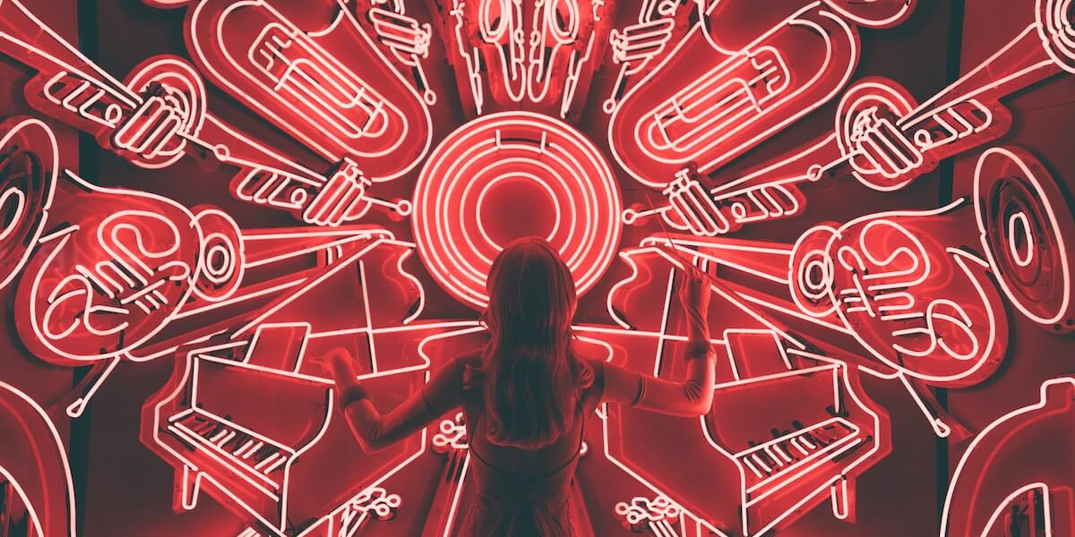 woman standing in front of red neon lights of musical instruments