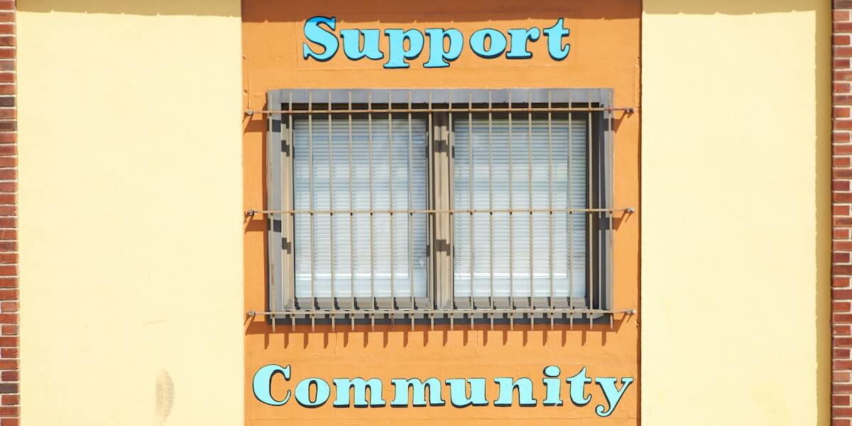 window with text painted above and below saying support community