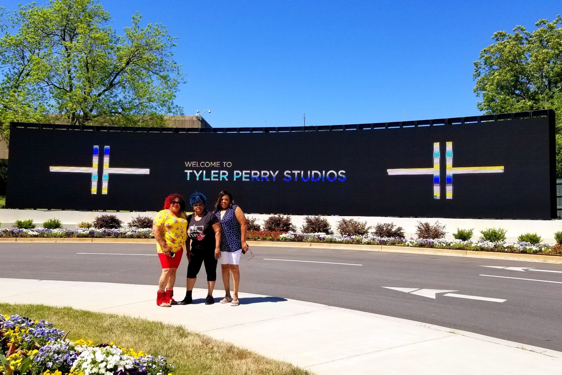 Three women stand outside the Tyler Perry Studios in Atlanta