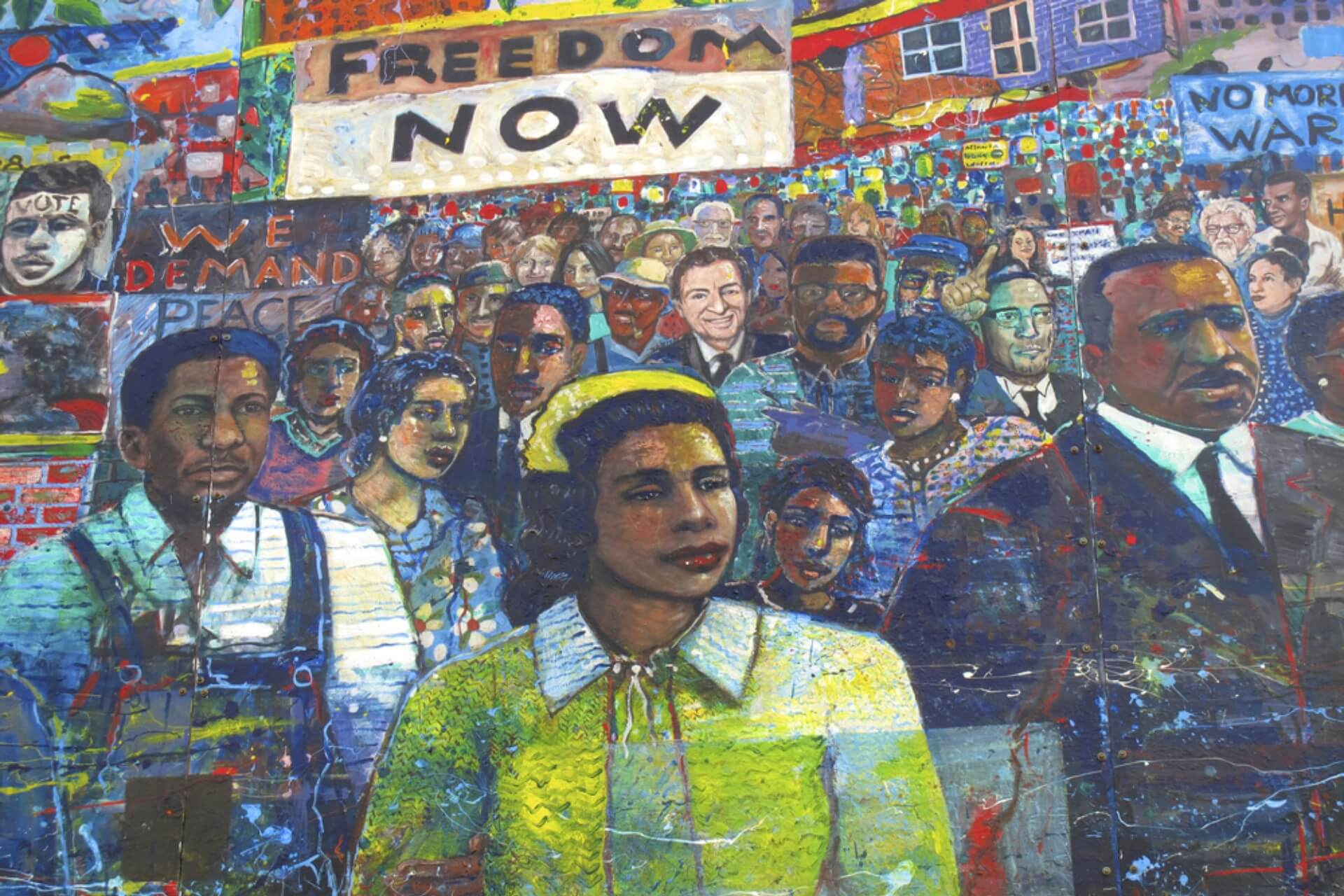 A mural if a woman and a crowd on a wall in Atlanta.